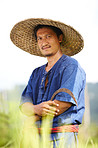 Portrait of a Thai rice farmer holding a scythe and wearing a traditional hat