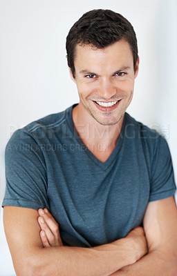Buy stock photo Portrait of cute young man leaning against the wall with arms crossed