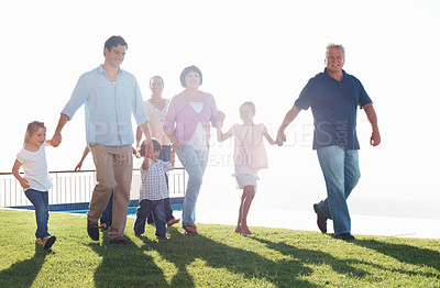 Buy stock photo Family portrait of three generation family holding hands while walking on grass