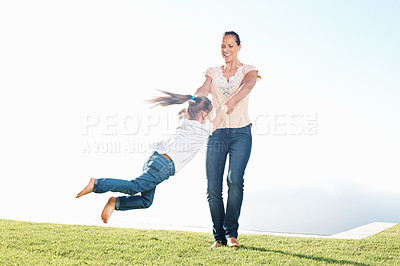 Buy stock photo Mother with happy little daughter whirling on green sunny meadow