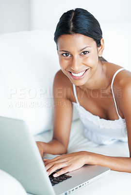 Buy stock photo Smiling mixed race woman relaxing at home using laptop