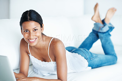 Buy stock photo Mixed race woman browsing internet on laptop while lying on couch