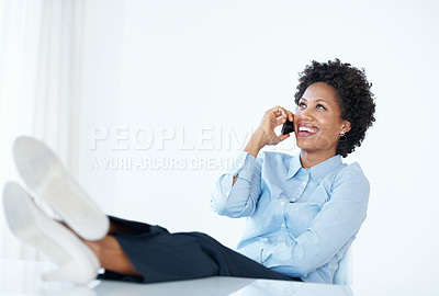 Buy stock photo Smiling African American female executive using cellphone with legs on desk