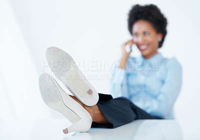 Buy stock photo Successful business woman using cellphone at work with legs on desk