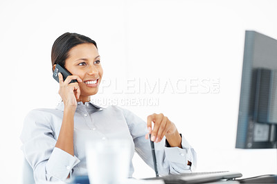 Buy stock photo Mixed race business woman using mobile phone while looking at computer screen