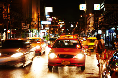 Buy stock photo Taxi traveling down a busy street in Thailand at night