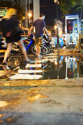 Buy stock photo Tourist jumping over puddles to cross the street in Thailand