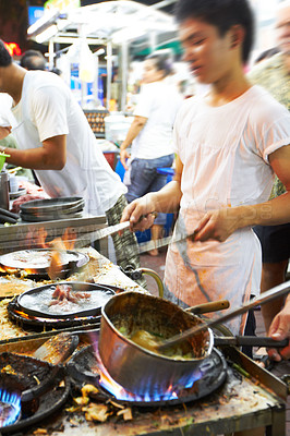 Buy stock photo Chefs in a Thai restuarant preparing food on gas stovetops