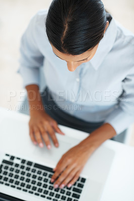 Buy stock photo High angle view of mixed race business woman using laptop at office desk