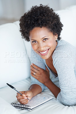Buy stock photo Relaxed African American woman in living room writing on notepad