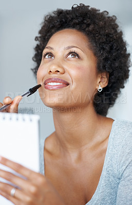 Buy stock photo Closeup of attractive African American woman thinking while writing in notepad