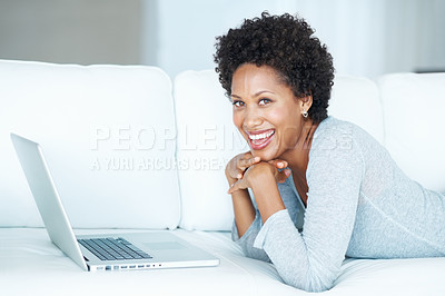 Buy stock photo Gorgeous African American woman using laptop while lying on sofa