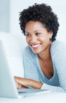 Buy stock photo Attractive young woman smiling while using laptop in living room