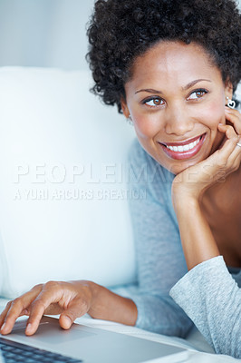 Buy stock photo Beautiful African American woman thinking while using laptop on couch