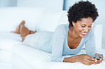 Smiling woman text messaging on couch