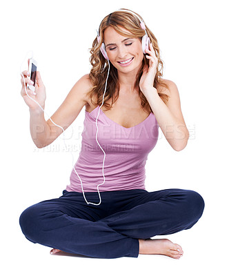 Buy stock photo Studio shot of a young woman sitting and listening to music through her headphones