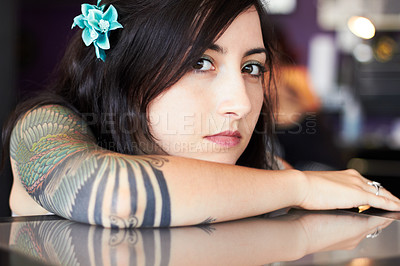 Buy stock photo A young tattoo artist showing off her half-sleeve tattoo while resting her head on her arm