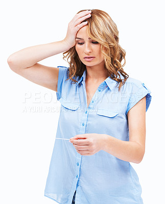 Buy stock photo A beautiful young woman looking shocked as she discovers she's pregnant