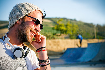 Buy stock photo Trendy skater talks to his mates on the phone in a skate park one late afternoon - copyspace
