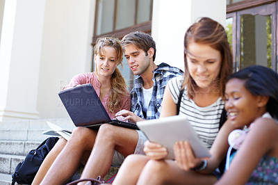 Buy stock photo Young students on their laptops while outside of their college