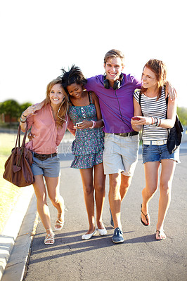 Buy stock photo Four young friends walking down the street while listening to music