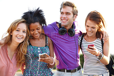 Buy stock photo Closeup of four friends listening to music and typing on their cellphones