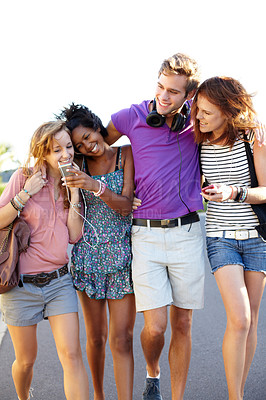 Buy stock photo Four friends sharing their music while walking down the street