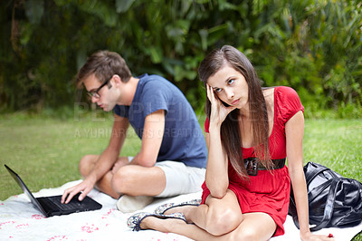 Buy stock photo Annoyed young woman looks away while her boyfriend types on his computer in the park