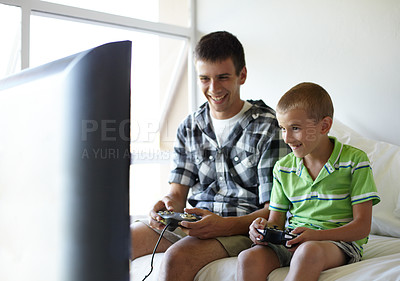 Buy stock photo Older brother playing video games with his younger brother