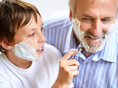 Buy stock photo Shot of a boy shaving his father's beard