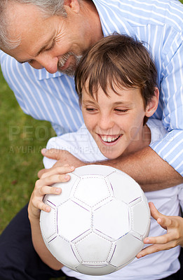 Buy stock photo Father embracing his young son after a game of soccer in the park