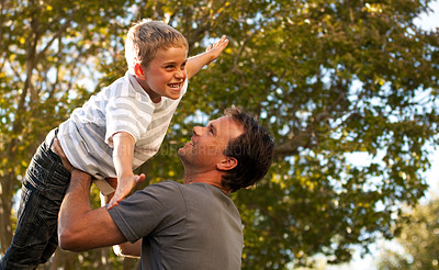 Buy stock photo Father giving his son imaginary airoplane rides while playing outside