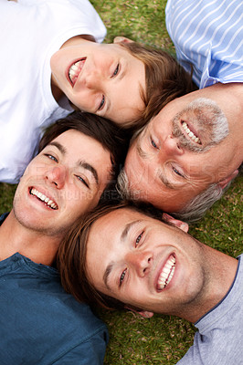 Buy stock photo Father and sons lying down on the grass with their heads beside one another