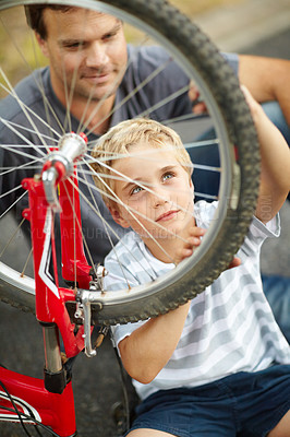 Buy stock photo Young father teaching his son how to change a bike puncture