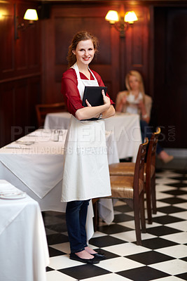 Buy stock photo Cute young waitress standing waiting to serve a customer - portrait