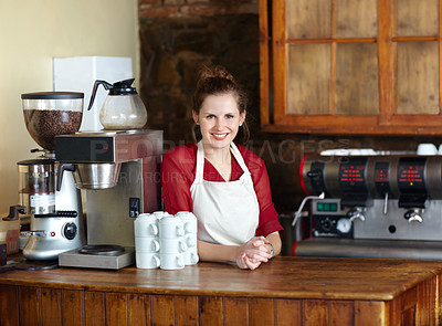 Buy stock photo Pretty young coffee steward behind the counter at work - portrait