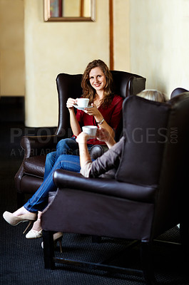 Buy stock photo Smiling young woman sitting in an armchair and enjoying coffee with friends