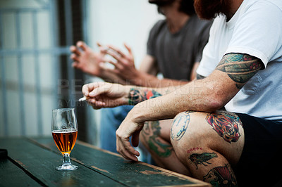 Buy stock photo Shot of young people smoking and drinking