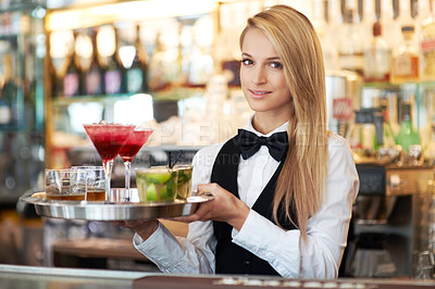 Buy stock photo Attractive young woman working as a bartender holding a tray of cocktails
