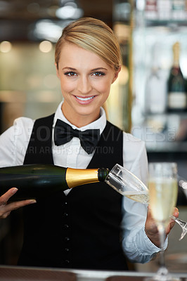 Buy stock photo Portrait of a barmaid pouring champagne for a special celebration
