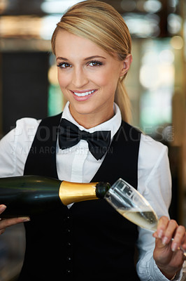 Buy stock photo Attractive waitress pouring champagne into a champagne glass smiling at the camera