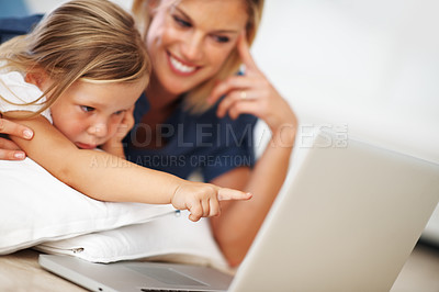 Buy stock photo Closeup of cute little girl using laptop with mother at home, pointing at screen