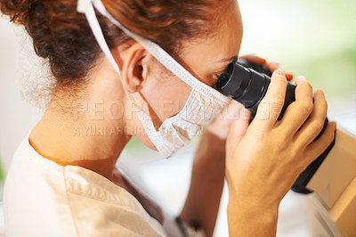 Buy stock photo Closeup of young female researcher looking into a microscope