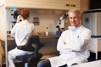 Buy stock photo Male researcher sitting with a assistant working on microscope in background at the lab