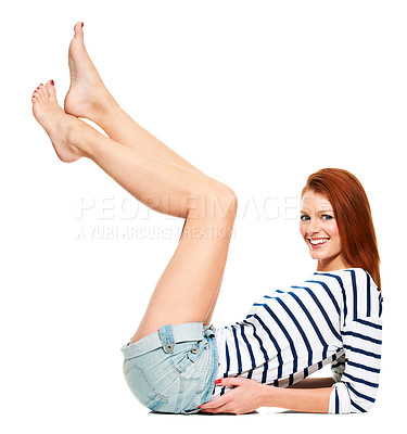 Buy stock photo Portrait of an attrcative young redhead leaning on her elbows with her legs in the air