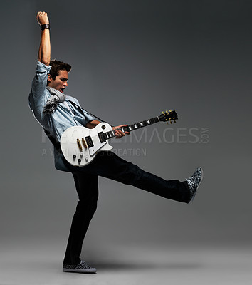 Buy stock photo Handsome young guitarist lifting his one leg and arm in the air in a flashy ending to a guitar solo