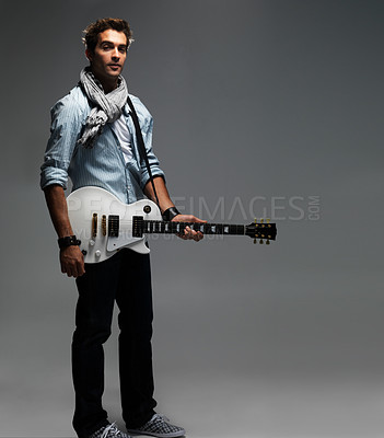 Buy stock photo Young handsome man with an electric guitar strapped to his chest - copyspace