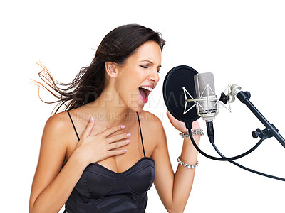 Buy stock photo Lovely young brunette singing into a microphone covered by a pop-shield - copyspace