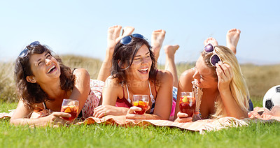 Buy stock photo A group of friends lying on a blanket outside and enjoying a drink together