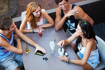 Buy stock photo Group of teens enjoying milkshakes and beverages while at an outdoor restaurant - high angle